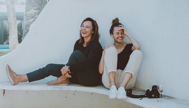 two girls sitting in front of a wall
